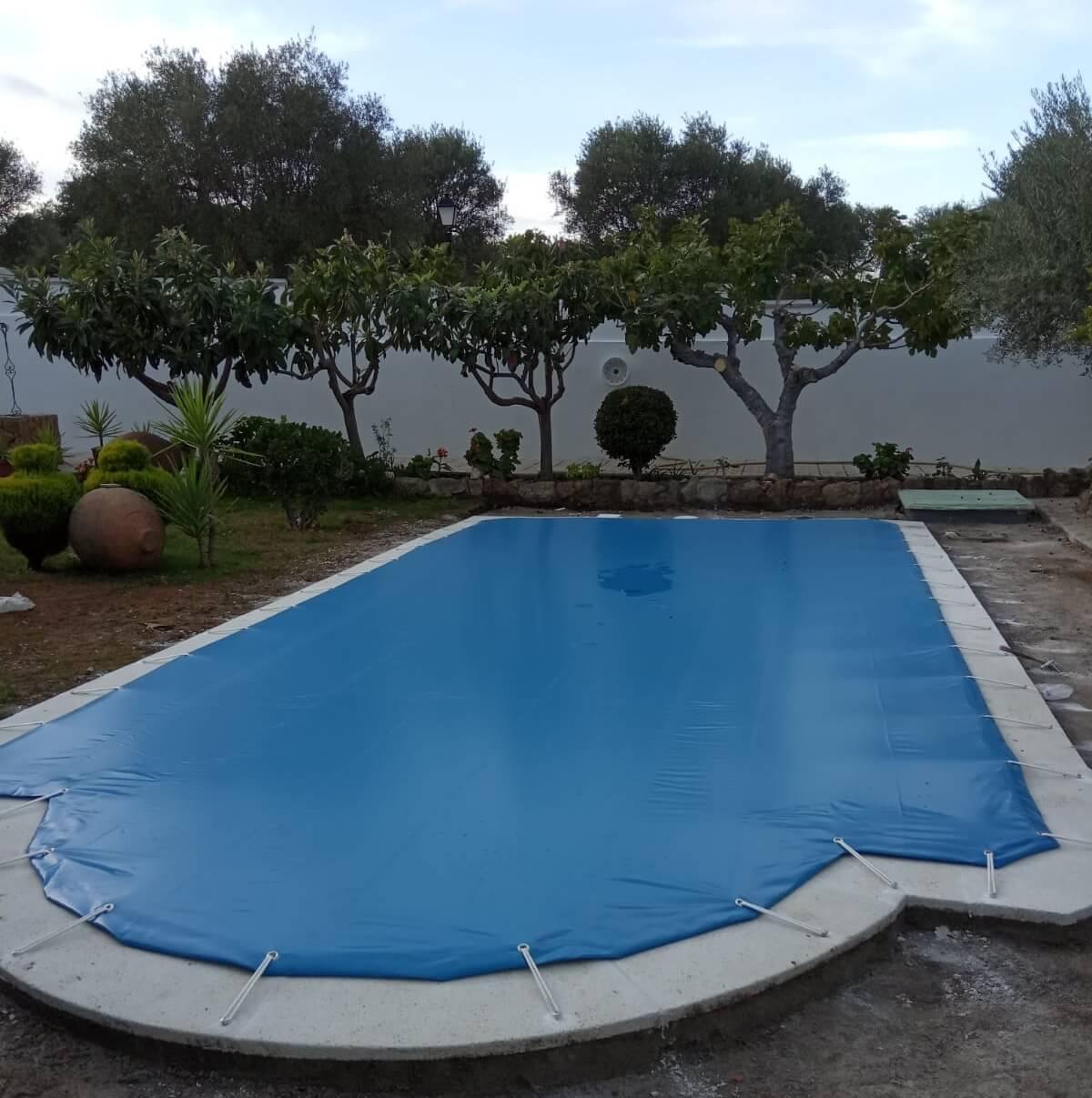piscina exterior cubierta con lona de protección azul para el mal tiempo