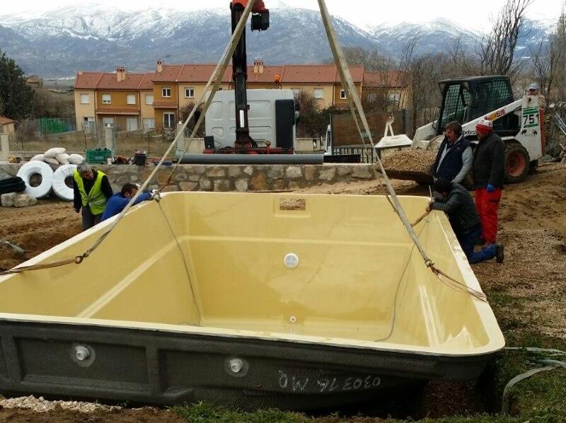 Operarios colocando una piscina de poliester en un jardín